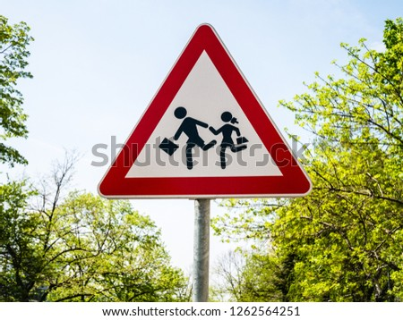 European road sign caution children crossing the street, over blue sky background