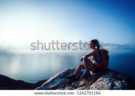 Young woman hiker at sunrise seaside mountain peak Royalty-Free Stock Photo #1262701186