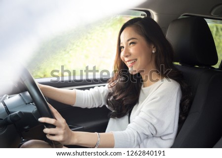 Asian women driving a car and smile happily with glad positive expression during the drive to travel journey, People enjoy laughing transport and relaxed happy woman on roadtrip vacation concept #1262840191
