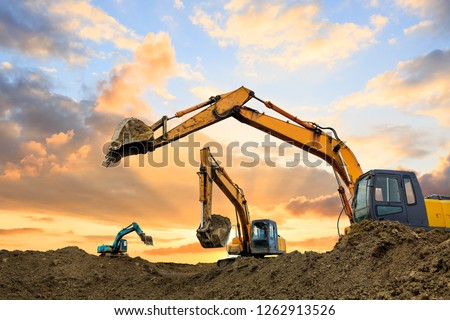Three excavators work on construction site at sunset Royalty-Free Stock Photo #1262913526