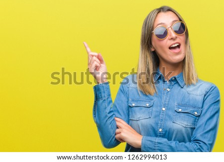 Young beautiful woman wearing sunglasses over isolated background with a big smile on face, pointing with hand and finger to the side looking at the camera. #1262994013