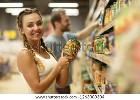 Charming and beautiful young woman with braids holding jar with beans. Female customer standing near shelves with cans, looking at camera and smiling. Background of man taking jar from shelf. #1263000304