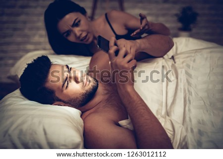Couple in Love in Bed, Man Using Mobile Phone. Spending Time with Each Other. Woman and Man Lying on Bed in Bedroom. Girlfriend and Boyfriend. Internet Conctent. Texting Message. Love Concept. #1263012112