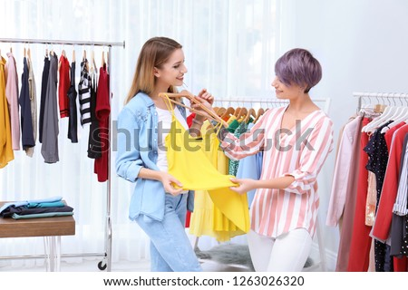 Young stylist helping customer to choose clothes indoors Royalty-Free Stock Photo #1263026320