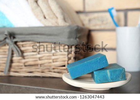 Dish with blue handmade soap bars on table in bathroom. Space for text Royalty-Free Stock Photo #1263047443