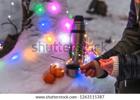 Thermos with hot tea, coffee, tangerines. girl holding sparklers in her hands, surrounded by colorful christmas lights, snow forest. active vacations outdoor hiking sport #1263115387