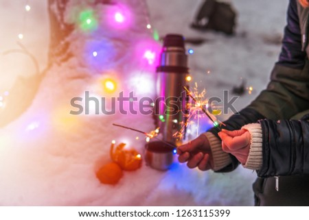 Thermos with hot tea, coffee, tangerines. girl holding sparklers in her hands, surrounded by colorful christmas lights, snow forest. active vacations outdoor hiking sport #1263115399