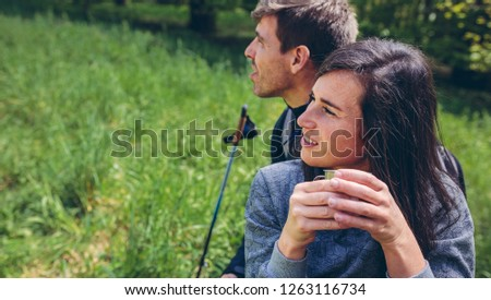 Young couple pausing to drink coffee while doing trekking outdoors enjoying nature #1263116734