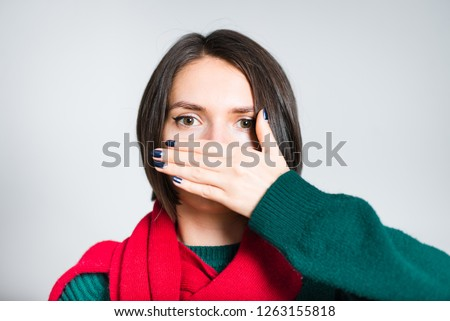 beautiful girl covers her mouth with her hand, secret, red scarf for New Year and Christmas, close-up over gray background #1263155818