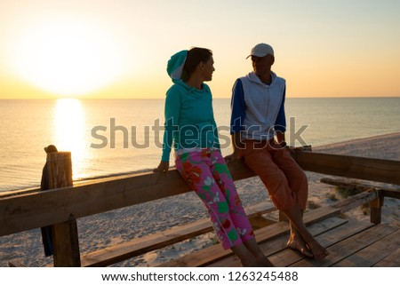 Romantic couple relaxes on a bungalow veranda, admiring the sunset over the sea and enjoying life. Amazing travel to the seashore. Backlight. #1263245488