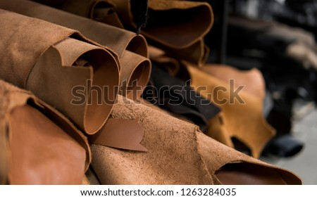 Different pieces of leather in a rolls. The pieces of the colored leathers. Rolls of natural brown red leather. Raw materials for manufacture of bags, shoes, clothing and accessories. #1263284035