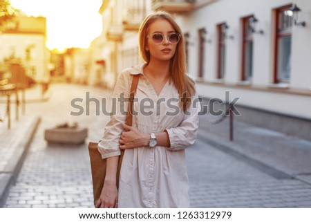 Attractive hipster young woman in stylish sunglasses in a stylish white dress with a fashionable brown handbag walks through the vintage streets of the city on a sunset background. Fashionable girl #1263312979