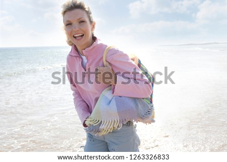 Smiling woman walking by ocean on beach with picnic basket at camera #1263326833