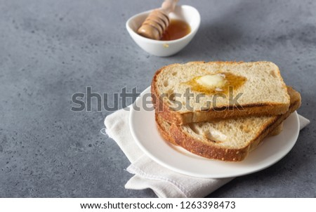 Slices of toast bread and butter with honey on grey stone background #1263398473