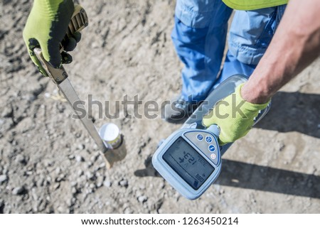 How to trace power cables with the cable Finder. Electric technical worker with power cable fault location carries out a work of tracing the new electric line with a colored spray can. #1263450214