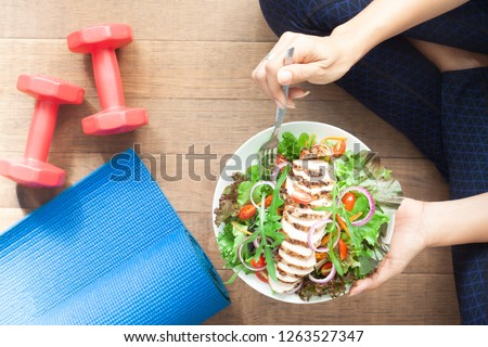 Top view healthy girl eating chicken salad. Dumbbells and yoga mat on the floor #1263527347