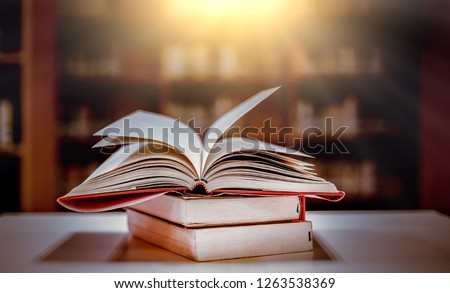 Stack of books in the library and blur bookshelf background #1263538369