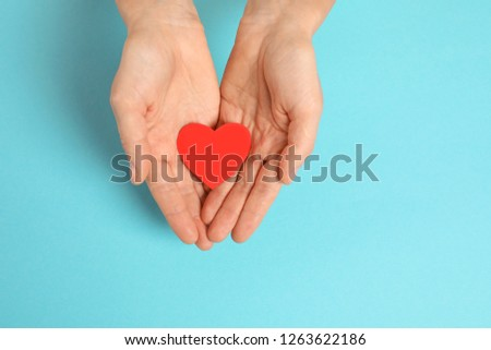 Woman holding paper heart on color background, top view with space for text #1263622186