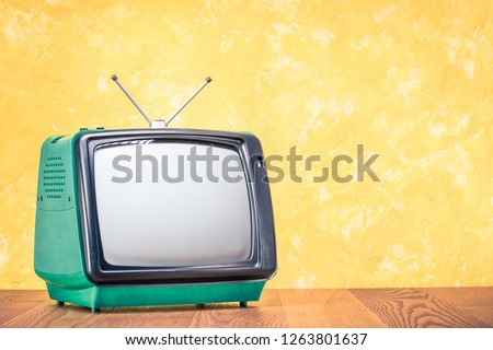 Retro old outdated green TV receiver from circa 70s on wooden table front textured yellow concrete wall background. Vintage style filtered photo