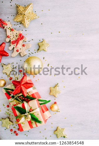 Christmas background with confetti, christmas balls, and red gift boxes on the white wooden board #1263854548