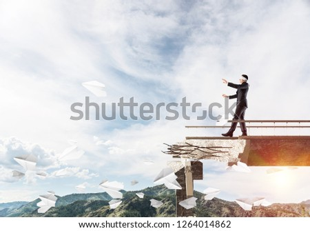 Businessman walking blindfolded on concrete bridge with huge gap as symbol of hidden threats and risks. Skyscape and nature view on background. 3D rendering. #1264014862
