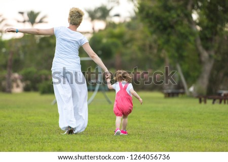 Young Mother and cute little daughter enjoying free time playing outside at backyard on the grass, happy family in nature concept #1264056736