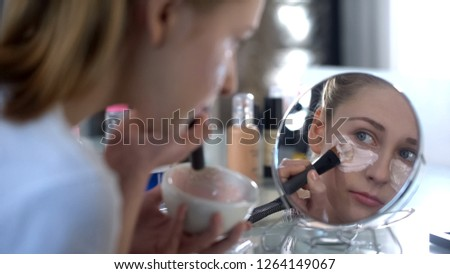 Pretty young woman carefully putting hyaluronic alginate mask under eyes, beauty #1264149067