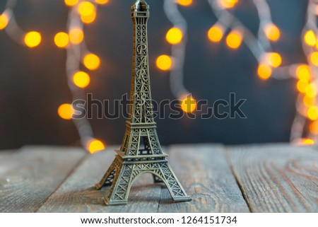figure of the Eiffel tower on the background of a glowing garland #1264151734
