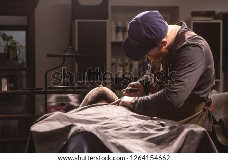 Moscow, Russia - December, 2018: Barber cuts beard of client who lies in Barber chair. Hairdresser at work. Barbershop View From Outside. #1264154662