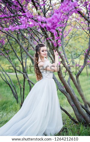 Luxurious and stylish bride poses in the garden among purple flowers. Happy bride with beautiful and long hair. An important day in life, strong emotions. #1264212610