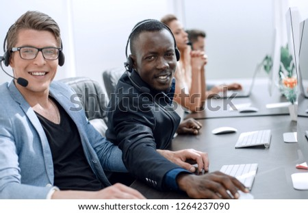 call center operators sitting at their Desk. #1264237090