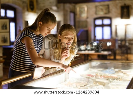 Girl with woman looking with interest at art objects under glass in museum, using guidebook Royalty-Free Stock Photo #1264239604