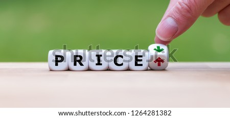 Hand is turning a dice and changes the direction of an arrow, symbolizing that the price is going down (or vice versa) #1264281382