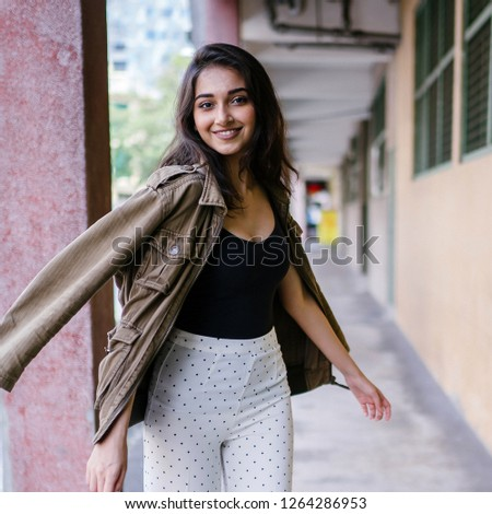 A beautiful, stylish, tall and elegant Indian Asian woman walks down a corridor and spins around to smile at the camera. She is beautiful and confident.  #1264286953