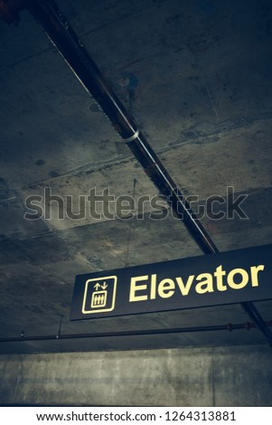 Elevator sign in parking garage (Vertical Frame).