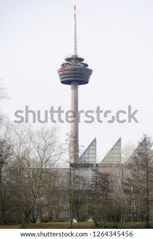 Cologne, Germany - March 11 2017: Colonius Tower in Cologne / Koln Germany, view through the trees in winter, daytime with overcast sky #1264345456