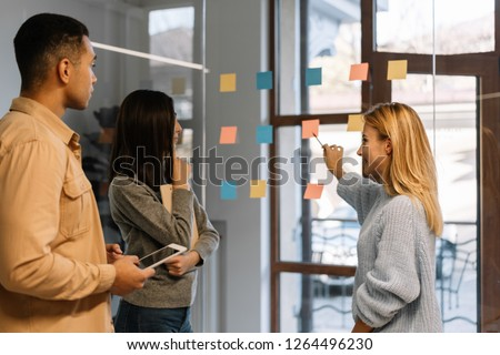 Creative team working together for startup project. Team building. Strategy planning. Brainstorming. Collaborate. Successful scrum master showing finger on sticky note, helping team reach consensus. #1264496230