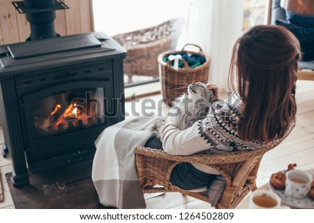 Human with cat relaxing in wicker armchair by the fire place in wooden cabin. Warm and cozy winter holiday concept. #1264502809