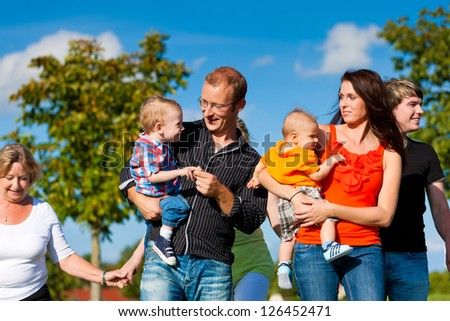 Family and multi-generation - mother, father, children and grandmother having fun on meadow in summer #126452471