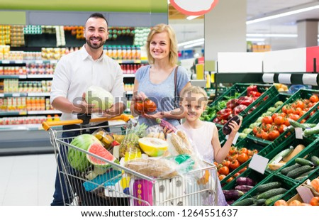 cheerful european family shopping various fresh vegetables in supermarket