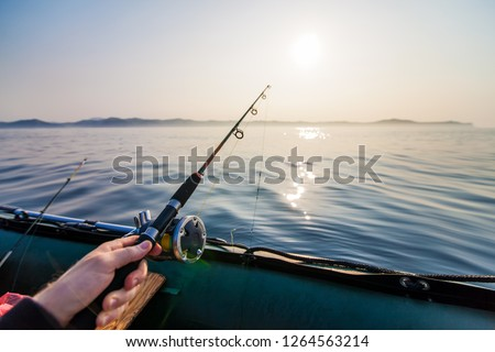 Fish-rod in fishermen's hand. Fishing  at inflatable boat #1264563214