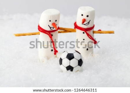 Two snowman on a blurred light background and a soccer ball in the foreground
