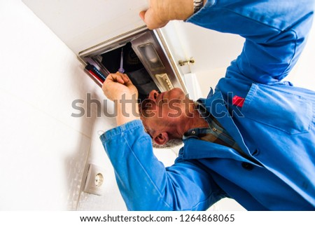 Professional handyman is working and fixing the vent hood in house #1264868065