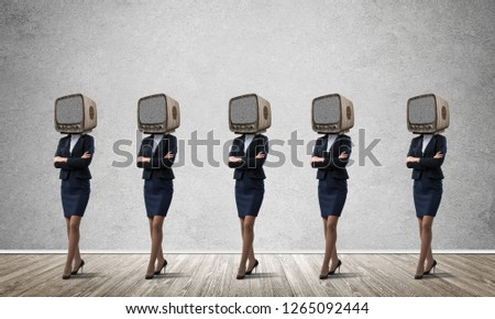 Business women in suits with old TV instead of their heads keeping arms crossed while standing in a row in empty room with gray wall on background. #1265092444