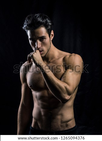 Handsome muscular shirtless young man standing confident, front view, looking at camera #1265094376