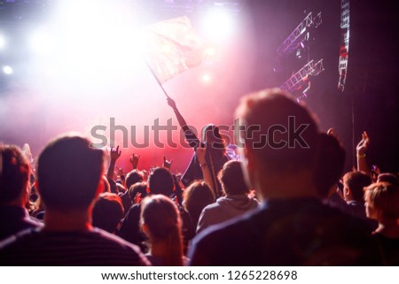 Rock concert, people in the hall on the background of the stage and spotlights. Fans waving the flag and making hands up #1265228698