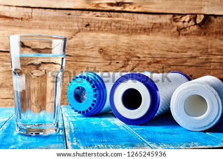 Water filters. Carbon cartridges and a glass of water on a wooden background. Household filtration system. #1265245936