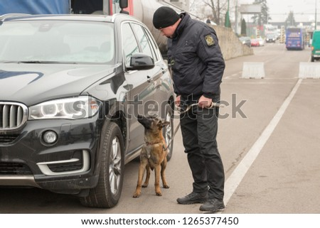SHEGINI, UKRAINE - NOVEMBER, 2018: Ukrainian border guard with a service dog inspects vehicles at the checkpoint at the Ukrainian-Polish border, Shegini-Medyka, 80 kilometers west of Lviv #1265377450