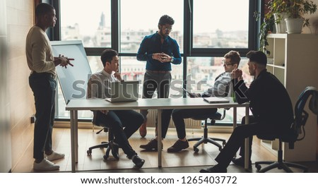 Multiracial male staff of architectural and design bureau communicating in modern loft office with panoramic view, discussing individual orders of the clients on design and planning of interiors. #1265403772