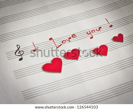 """Words """"I love you !"""" in shape of music notes in the music note book with red hearts"""